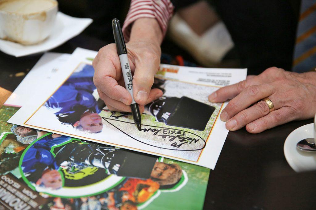 Ллойд Кауфман ставит автограф на фирменных принтах